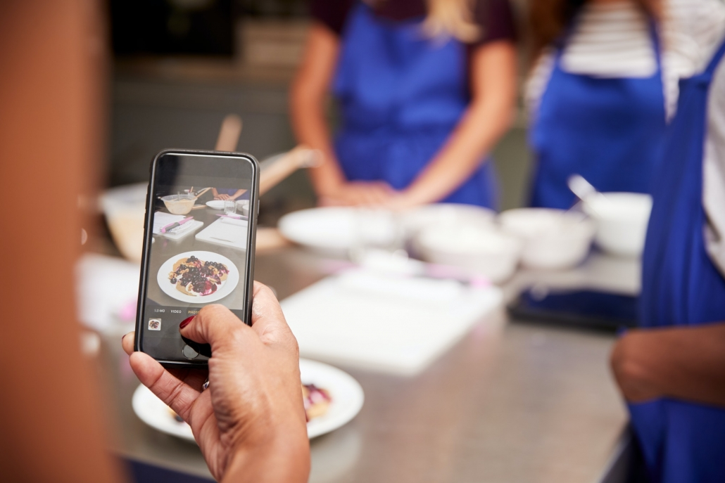 Close Up Of Woman Taking Photo Of Pancake Dish For Social Media In Cookery Class